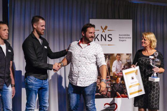 Juryvoorzitter Jord Althuizen feliciteert de mannen van Slagerij van Tilburg, terwijl Marian Lemsom van KNS de felbegeerde trofee aanreikt.