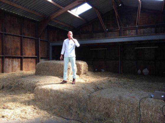 Televisiekok René Pluijm spreekt op zijn eigen ludieke wijze de bezoekers toe vanaf een stapel hooibalen.