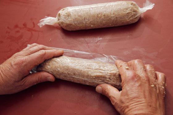 Rol het deeg strak en stevig op in plastic folie.